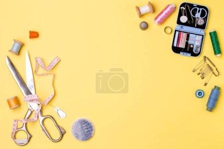 Photo pour Composition avec filetages et accessoires de couture - ciseaux, centimètre, broches sur fond jaune. Concept pour la couture et la couture - image libre de droit