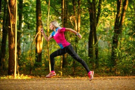 Photo pour Photo du côté de la femme sportive qui traverse le parc entre les arbres matin d'été. - image libre de droit