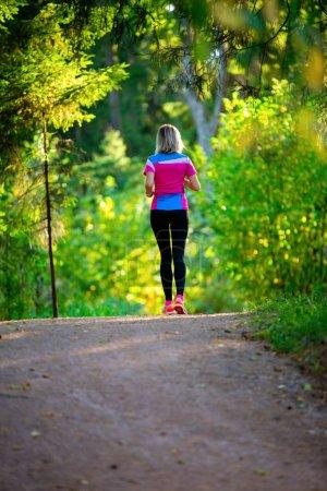 Photo pour Photo de l'arrière de la femme athlète blonde, traversant le parc entre les arbres matin d'été. - image libre de droit