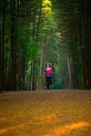 Photo pour Photo de l'arrière de la femme sportive qui traverse le parc entre les arbres matin d'été. - image libre de droit