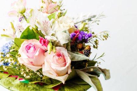 Фото романтического букета розовых роз, лилий, зеленых листьев на белом фоне