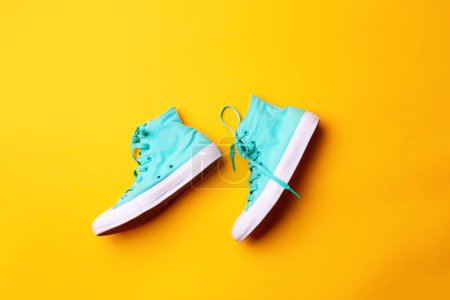 Photo for Pair of stylish sneakers laing on yellow background. Concept of fashion and design, shopping. - Royalty Free Image