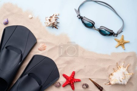 Photo pour Lunettes de natation et palmes sur le sable avec des coquillages et des étoiles de mer. Concept de holliday d'été et de natation - image libre de droit