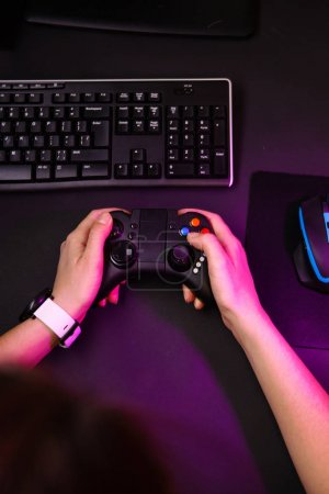 Photo for Female hands playing a computer game with a game joystick. Gamer workspace concept. - Royalty Free Image