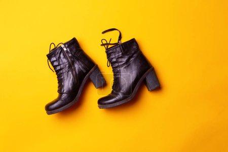 Foto de Elegantes botas de tacón negro para mujer. Vista superior de las botas negras sobre un fondo amarillo. Concepto de moda y diseño, compras - Imagen libre de derechos
