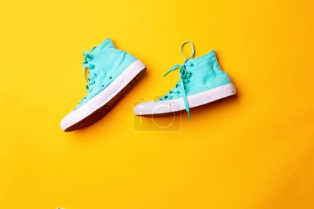 Pair of stylish sneakers laing on yellow background