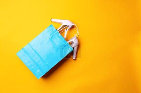 Photo pour Vue du dessus du sac à provisions bleu avec des chaussures élégantes sur fond jaune. Concept de mode et de design, shopping - image libre de droit