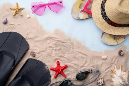 Photo pour Accessoires de plage - lunettes de natation, nageoires, tongs, lunettes de soleil et chapeau sur le sable avec des coquillages et des étoiles de mer. Concept de holliday d'été et de natation - image libre de droit