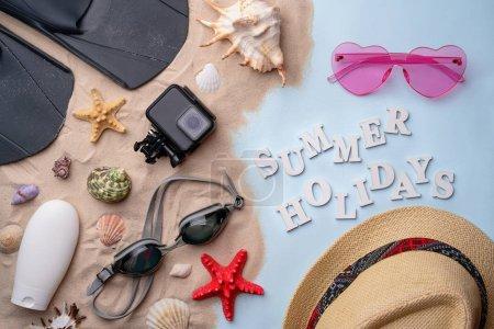 Photo pour Accessoires de plage - lunettes de natation, palmes, tongs, lunettes de soleil, chapeau, crème solaire et caméra d'action sur sable avec coquillages et étoiles de mer. Concept d'été holliday et natation - image libre de droit