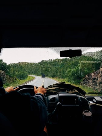 Photo for Image from passenger compartment of car driving along road among green trees in Norway on summer day - Royalty Free Image