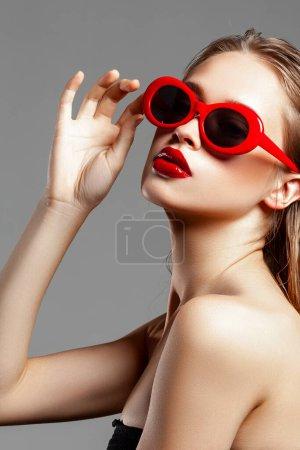 Photo pour Belle jeune fille aux lunettes de soleil rouges. Portrait beauté mode. Une peau parfaite - image libre de droit