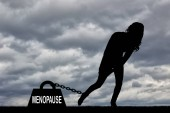 The silhouette of a woman and a heavy load of menopause is chained to her leg. Conceptual image of menopause in women