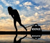 The silhouette of a sad woman and a heavy load of menopause is chained to her leg. Conceptual image of menopause in women
