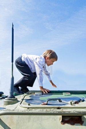 Photo pour Boy on the tank, boy in school uniform climbed onto a military tank, sunny day - image libre de droit