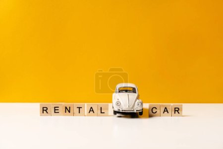 Photo for Toy white car on a white table with a yellow background, the inscription of wooden blocks. The concept of a rental car and car sharing. - Royalty Free Image