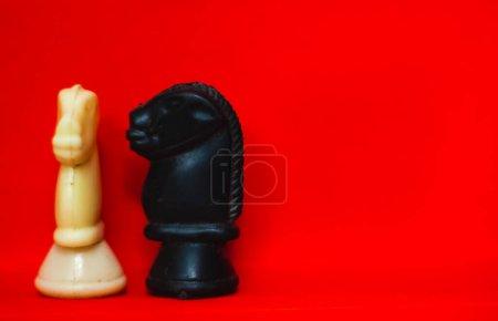 Pièces d'échecs chevaliers face à face pour un affrontement avec flou isolé sur fond rouge. Confrontation de pièces d'échecs.Pièces d'échecs chevaliers sur le terrain de guerre des échecs. Chevaliers d'échecs tête à tête