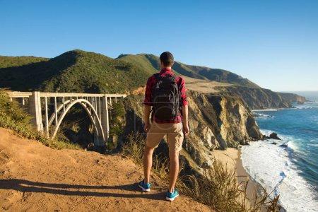 Photo pour Voyagez à Big Sur, homme Randonneur avec sac à dos profitant de la vue Bixby Bridge, Californie, États-Unis - image libre de droit