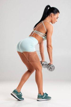 Photo pour Fitness femme faisant de l'exercice pour les fessiers sur fond gris. Entraînement de femme athlétique avec haltères - image libre de droit