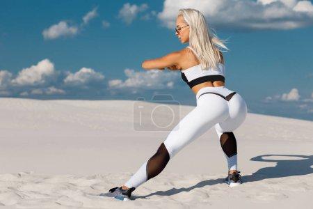Photo pour Fitness femme faisant des exercices de fentes pour la musculation des jambes entraînement. Fille active faisant un exercice de saut de jambe, en plein air - image libre de droit