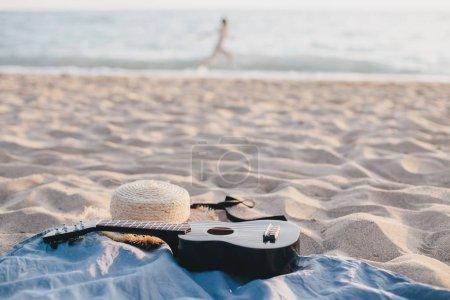 Photo pour Nature morte avec chapeau de paille et ukulélé sur la plage. Concept d'été . - image libre de droit