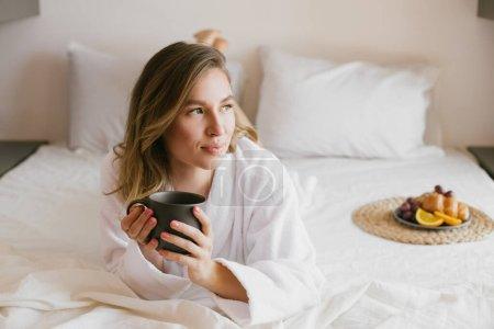 Photo pour Jeune belle femme portant un peignoir blanc petit déjeuner au lit avec café et croissant et fruits frais dans une chambre confortable. rituels du matin . - image libre de droit