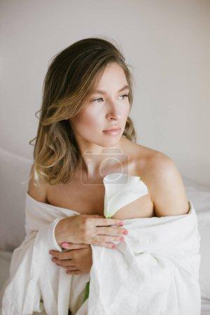 Photo pour Jeune belle femme enveloppée dans une couverture blanche relaxante dans une chambre confortable tenant dans sa main une fleur de lis de calla blanche. Beauté naturelle . - image libre de droit