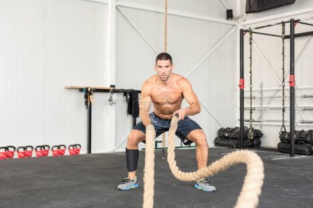 Photo for Men with battle ropes exercise in the fitness gym. CrossFit concept. - Royalty Free Image