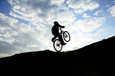 man using a bicycle as an acrobat;crazy biker