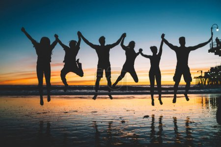 Silhouette of jumping friends enjoying summer vacations and youth lifestyle during scenery sunset, group of people holding hands and feeling happiness about friendship. Concept of friendship, success