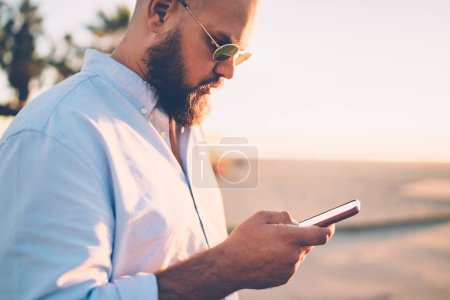 Bearded hipster guy holding mobile telephone making booking on website via application, close up of young man sending text message via smartphone chatting in social networks with friend on city street