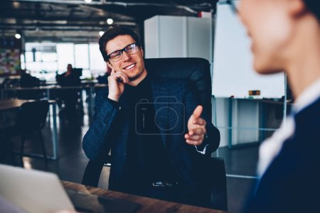 Cheerful male boss in formal wear having friendly talk with employee satisfied with her job,prosperous businessman gesture and smiling during conversation consultancy about successful startup idea