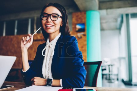 Half length portrait of cheerful businesswoman in formal wear sitting at working place holding pen satisfied with creative idea,prosperous female executive manager having successful career in finance