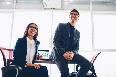 Photo pour Collègues de travail prospère en vêtements assis dans le bureau au cours de la réunion satisfaite des réalisations de l'entreprise, finances réussie de mâles et femelles partenaires heureux sur la coopération et des revenus budgétaires - image libre de droit