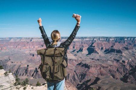Photo pour Vue arrière de la jeune femme avec sac à dos excité avec sentiment de liberté sur le sommet de la montagne explorer la nature de paysages sauvages, fille hipster wanderlust lever les mains heureux d'atteindre le sommet de la haute colline - image libre de droit
