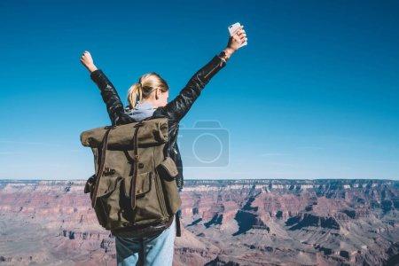 Photo pour Jeune voyageuse célébrant la réalisation d'atteindre le sommet de la montagne explorer le parc national de l'Arizona, fille hipster sentir la liberté levant les mains debout sur une falaise rocheuse sur la vallée dans le Grand Canyon - image libre de droit