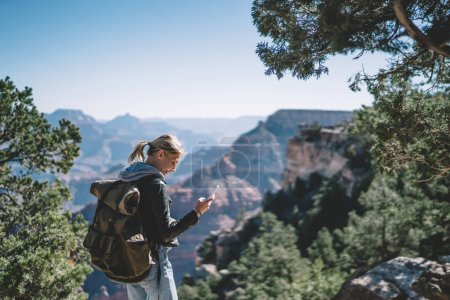 Smiling female tourist with backpack satisfied with having roaming mobile connection for communication in wild environment, hipster girl navigating during hiking tour using application on smartphone