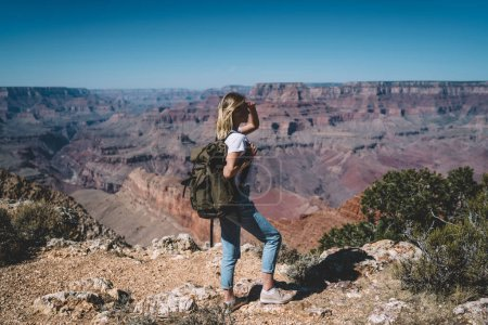 Female traveler with backpack enjoying trip while hiking on touristic route in wild environment, hipster girl wanderlust observing beautiful scenery of Arizona National Park standing on high hill peak
