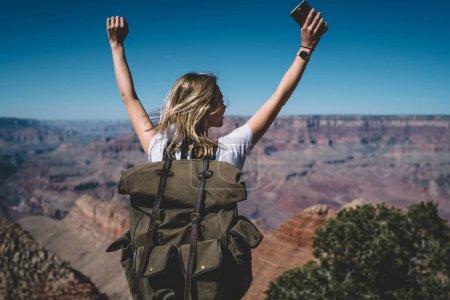 Photo pour Vue arrière de la fille hipster excitée debout sur le sommet de la haute montagne se sentant libre levant les mains vers le haut, voyageuse heureuse avec sac à dos célébrant l'accomplissement d'atteindre le sommet lors d'une randonnée aux États-Unis - image libre de droit
