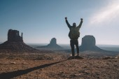 Hipster guy feeling freedom looking at beautiful natural landscape in Monument Valley, male traveler wanderlust excited with achievement of getting to viewpoint exploring wild environment of America
