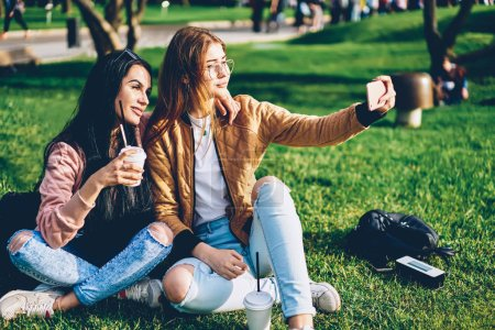 Cheerful best friends posing for making selfie on smartphone camera spending time together in park.Happy hipster girls in trendy outfit taking photos for uploading in social networks via mobile device