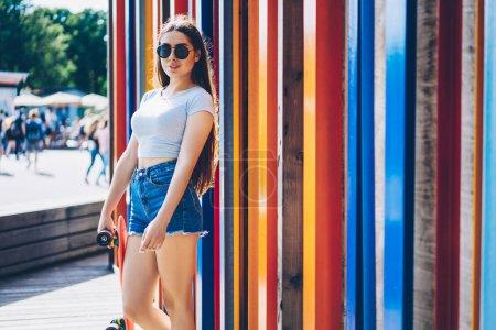 Photo pour Élégante fille hipster dans des lunettes de soleil debout près de milieux promotionnels colorés.Jeune femme en vêtements décontractés d'été tenant skateboard dans les mains près de la zone de publicité pour votre publicité - image libre de droit