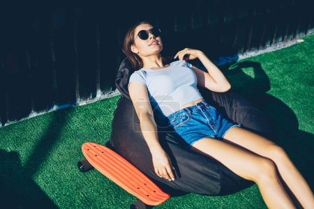 Photo for Casual dressed young woman in stylish spectacles lying on comfortable pouf enjoying sunny weather on lawn.Attractive hipster girl in sunglasses resting on green grass during summer holidays - Royalty Free Image