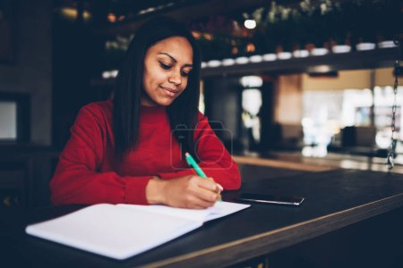Attractive young dark skinned model writing in notebook with blank pages spending time in cafe, Beautiful afro american businesswoman making financial notes planning budget for project in coffee shop
