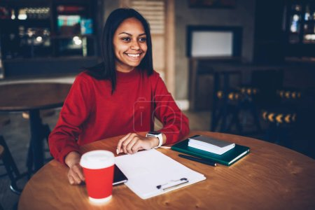 Successful young afro american manager making planning of business project during break in cafe.Prosperous female owner of coffee shop working with finance documentation organizing working process