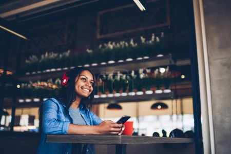 Cheerful afro american girl using free wifi access in cafe for listening music via application on mobile.Happy dark skinned student texting messages on cellular and enjoying playlist in headphones