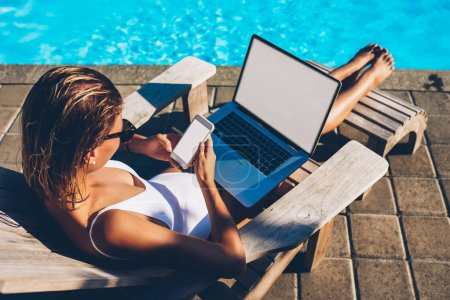 Attractive young woman resting on sunbed near blue swimming pool while reading incoming notification on smartphone and working freelance at laptop computer with blank copy space screen for content
