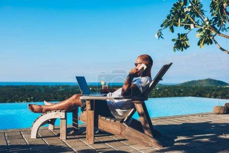 Photo pour Jeune homme d'affaires reposant sur un transat profitant de l'été dans un spa près de la piscine tout en travaillant à distance sur un ordinateur portable connecté à Internet sans fil et en parlant sur smartphone avec un partenaire - image libre de droit