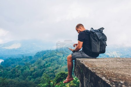 Photo for Male hiker with backpack sitting on top with beautiful scenery on asia environment with green vegetation and high mountains while using good internet connection for remote work on digital touch pad - Royalty Free Image