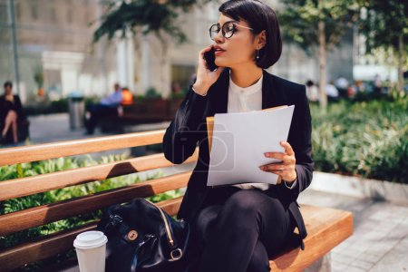 Busy female financial director in formal outfit talking with business partner on cellular while sitting on bench near office building holding documents with copy space for brand name or label in hands