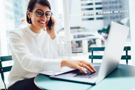Portrait of cheerful female executive manager in stylish eyewear sharing opinions about startup during phone conversation.Successful banker talking on mobile doing distance job in coffee shop